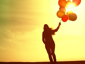 Woman with Baloons at Sunset