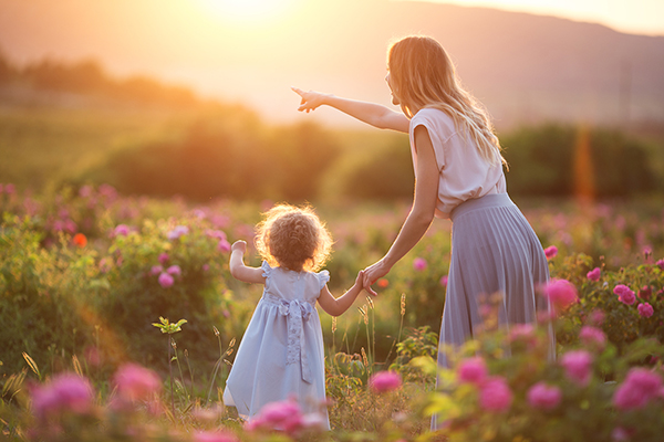 Beautiful child girl with young mother are wearing casual clothes walking in roses garden over sunset lights